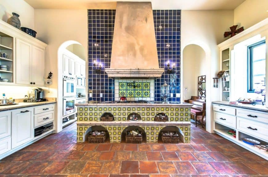 Southwestern kitchen features a blue tile backsplash accented with Talavera tiles and lighted by wall sconces.