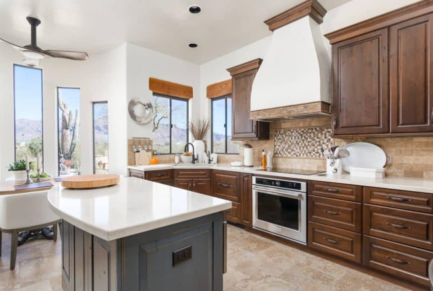 White kitchen with dark wood cabinetry and a blue distressed kitchen island topped with white marble. It has glass windows where you can enjoy the beautiful sight of the mountain.