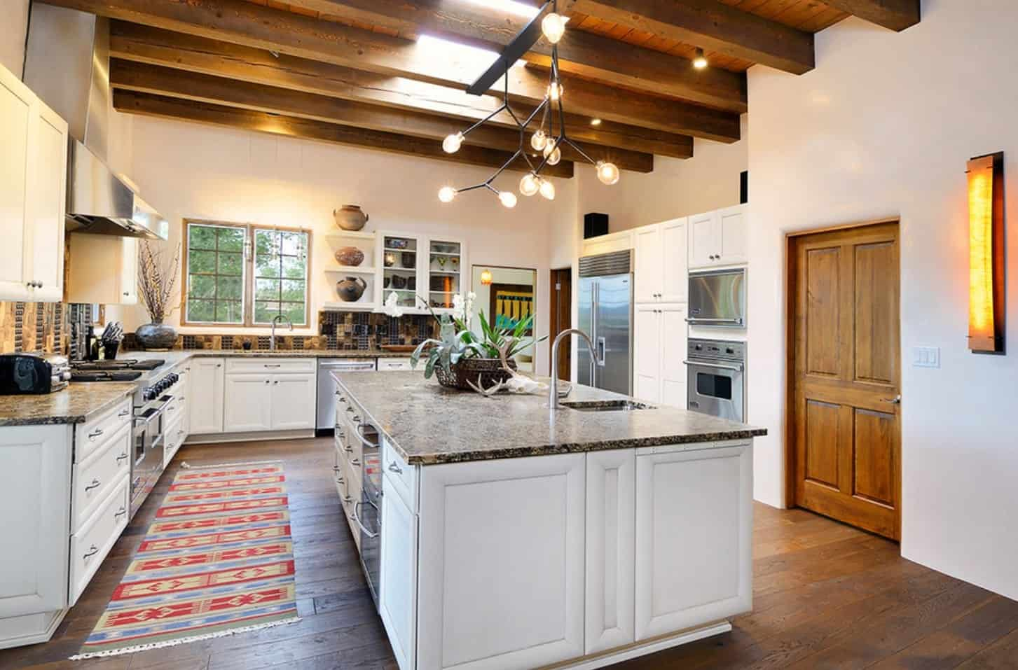 White kitchen with wood beam ceiling and hardwood flooring. It features a statement chandelier that hung over the breakfast island.