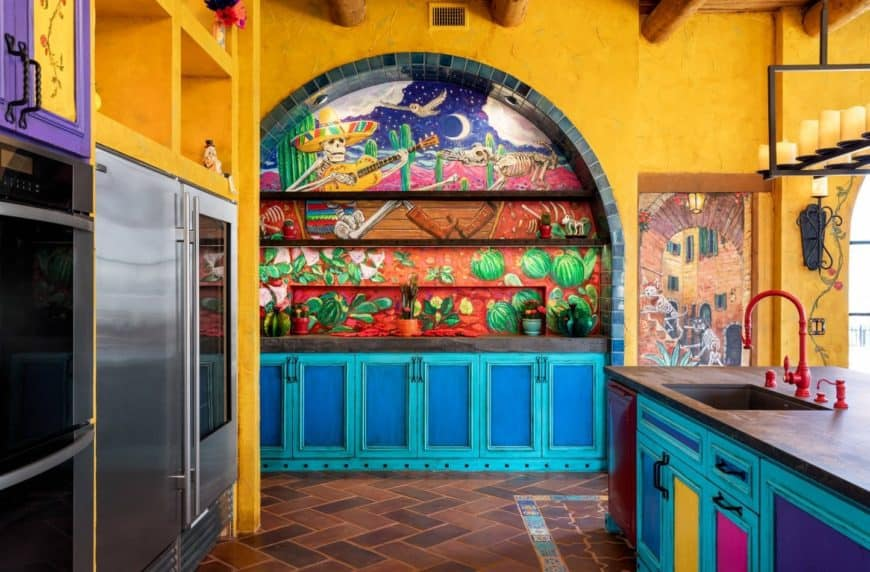 Mexico inspired kitchen accented with an arched mural lined by black brick tiles against the yellow walls. It includes a tiled flooring with herringbone pattern and multi-colored cabinetry.