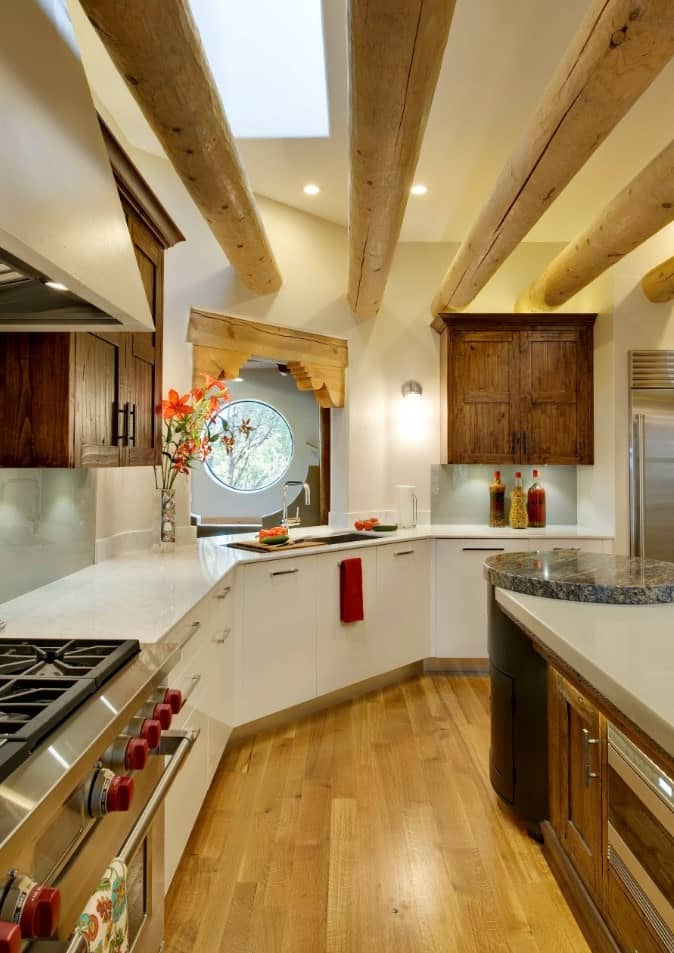 Curved kitchen with dark wood upper cabinetry along with white lower cabinetry. It has huge rounded wood beams and a breakfast island with a circular end.