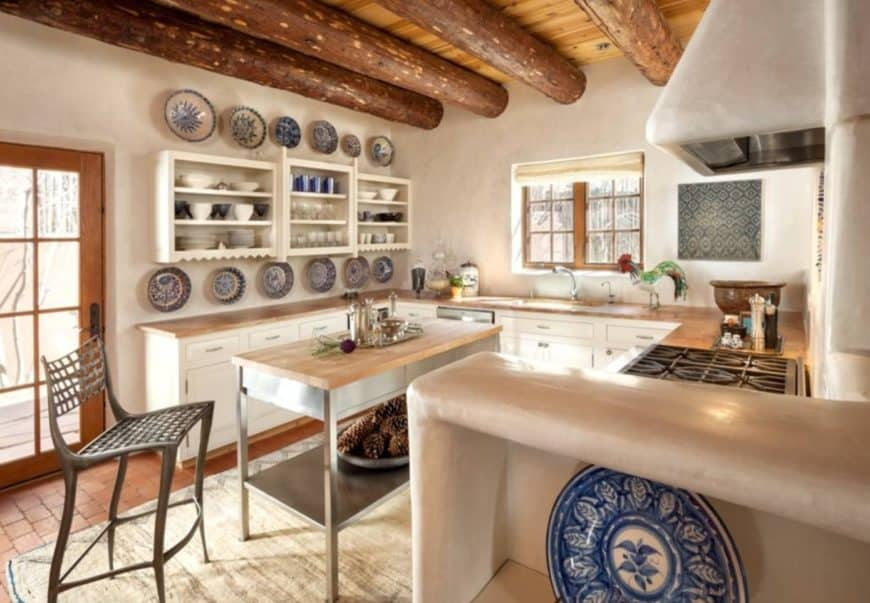 Southwestern kitchen features white cabinetry topped with wood counter and decorated with ceramic dinnerware.