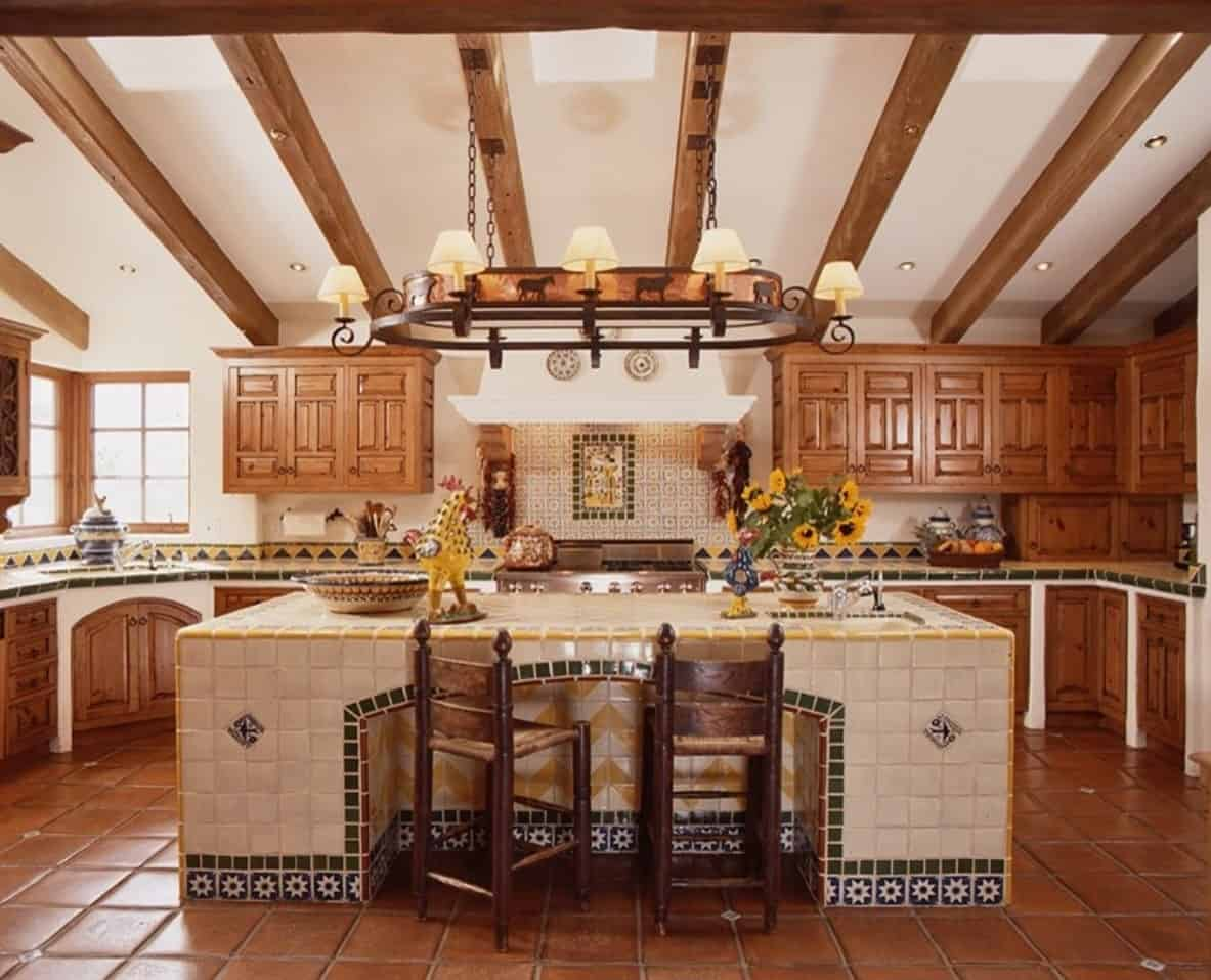Southwestern kitchen with a Mexican touch. Wooden chairs sit on a tiled breakfast island over a slate flooring.
