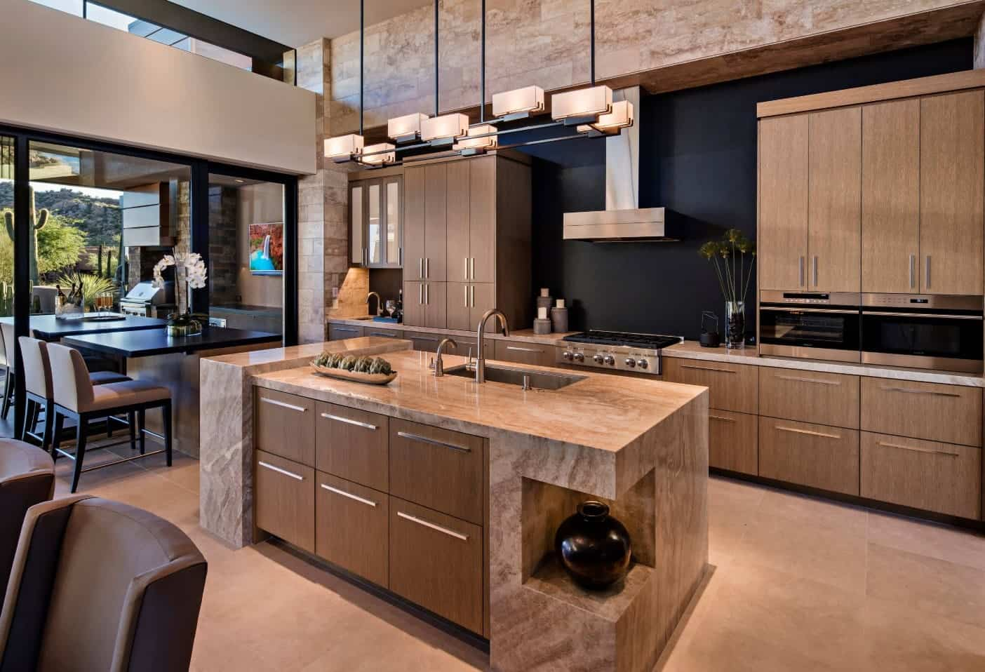This kitchen boasts a marble breakfast island illuminated by an industrial chandelier. It includes a stainless steel vent hood fixed to the black wall.