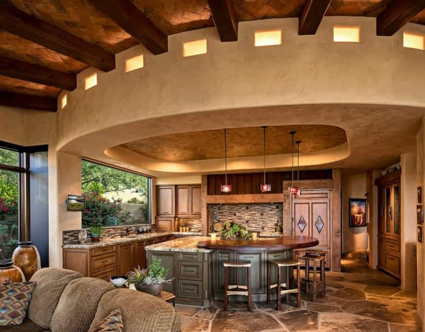 Magnificent kitchen boasts a breakfast island with raised countertop and lighted by pendant lights that hung from a tray ceiling. It has ceramic tile backsplash and beautiful stone flooring.