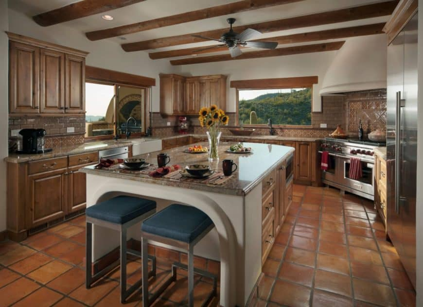 Southwestern kitchen with slate tile flooring and exposed beam ceiling. Blue metal stools sit on a breakfast island topped with marble counter.