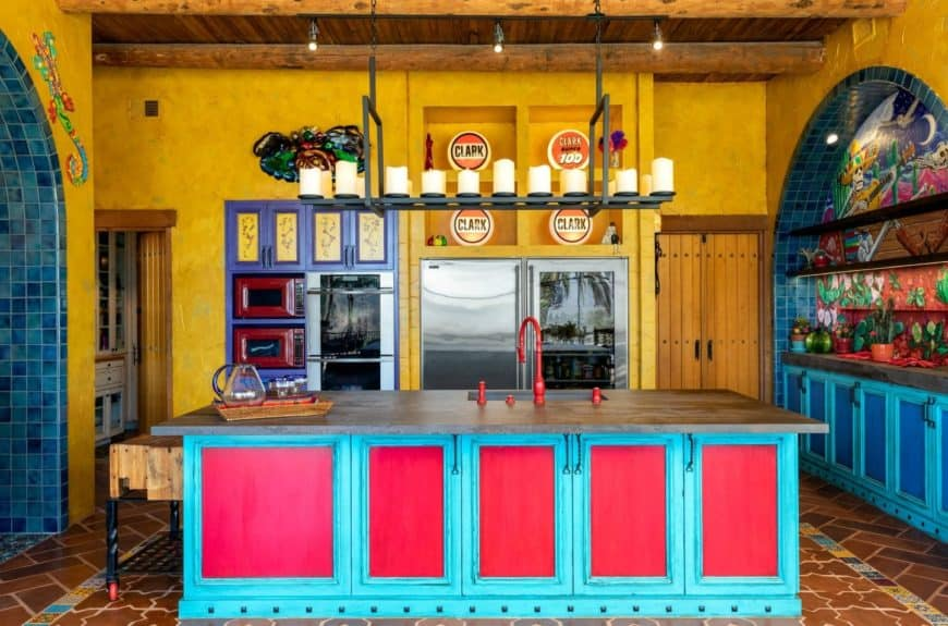 An oversized industrial chandelier hung over a two-toned breakfast island that's fitted with a sink and red fixtures in this colorful southwestern kitchen.