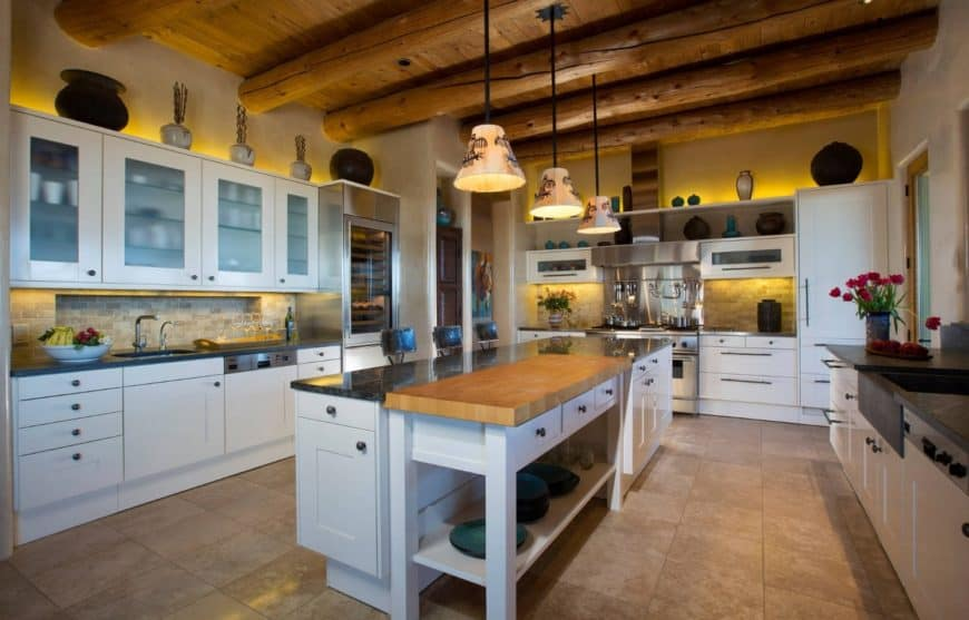 Southwestern kitchen features beautiful white cabinetry accented with warm lighting. It includes brick backsplash and lovely pendants that hung from a wood beam ceiling.