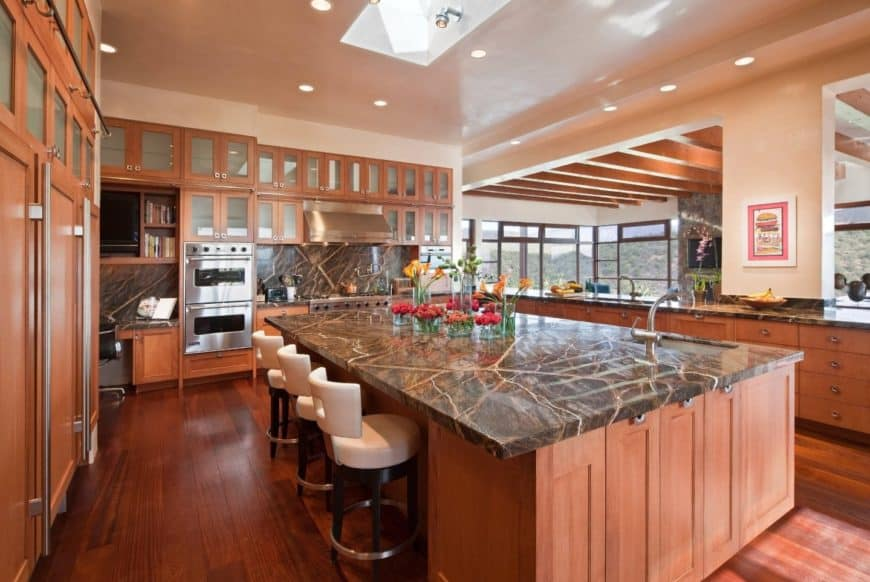Deluxe kitchen with large breakfast island topped with black marble granite that matches the backsplash and lined with white counter stools.