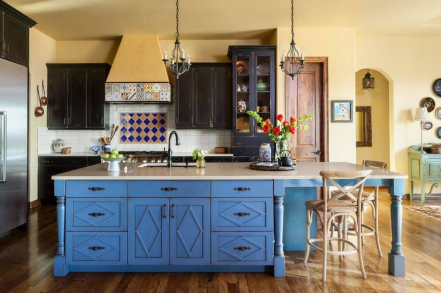 Southwestern kitchen features a blue kitchen island topped with white marble counter and fitted with a sink. It includes dark wood cabinetry and ceramic tile backsplash.