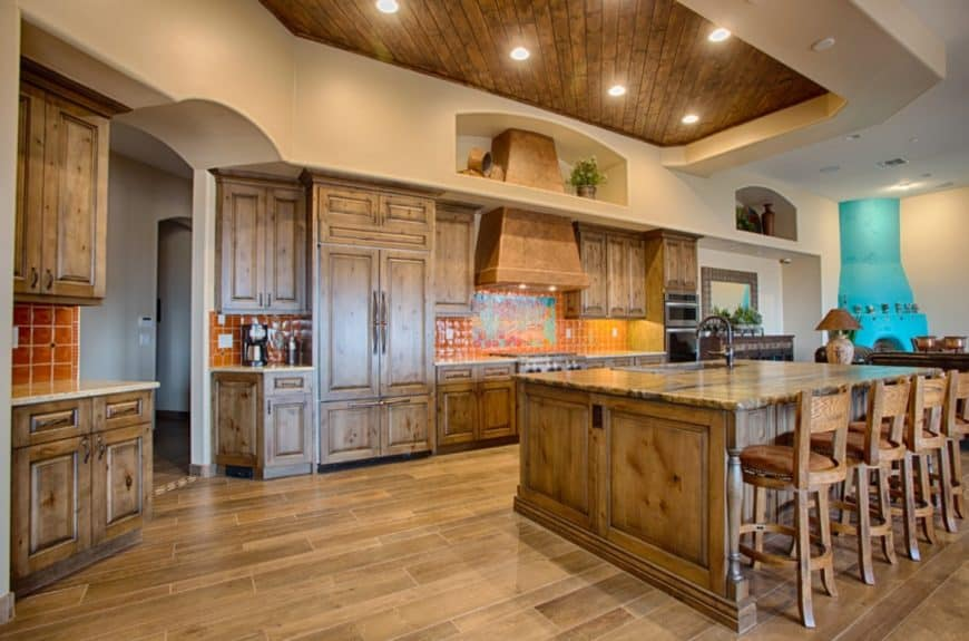 Spacious kitchen with a unified look. It is accented with red tiles backsplash designed with a mural beneath the vent hood.