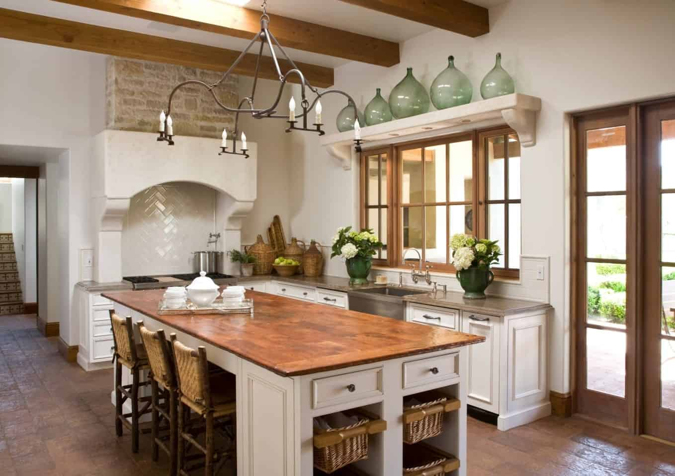 Wrought iron candle chandelier hung from an exposed wood beam ceiling over a breakfast island in this white kitchen. It feels airy and bright through the help of glass windows and doors and a skylight.