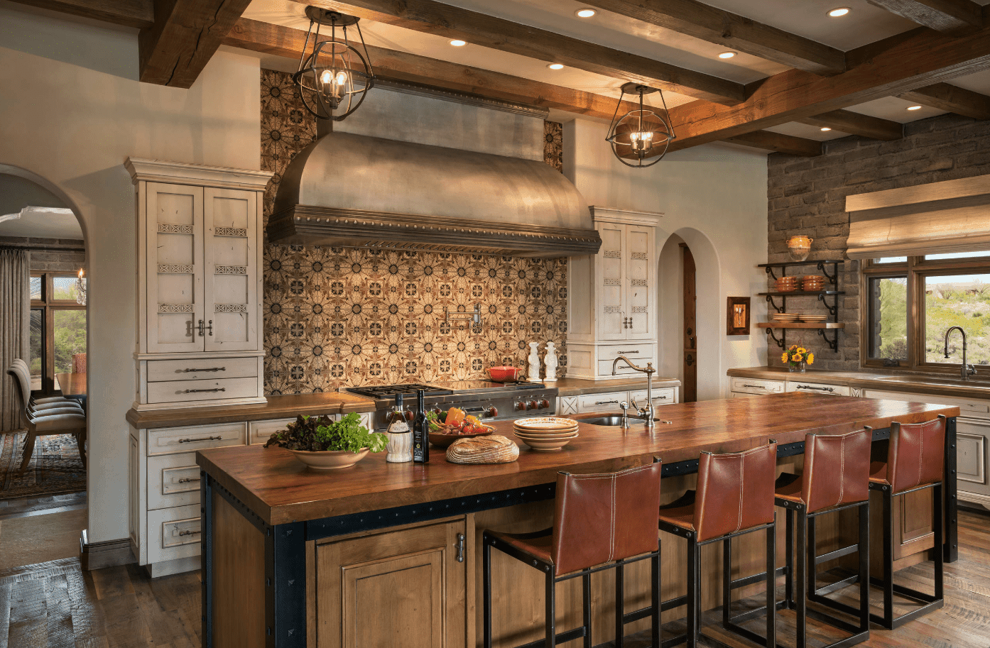 Attractive kitchen with a vent hood fixed to an eye-catching patterned backsplash. It includes a kitchen island bar topped with wooden counter and fitted with a round sink.