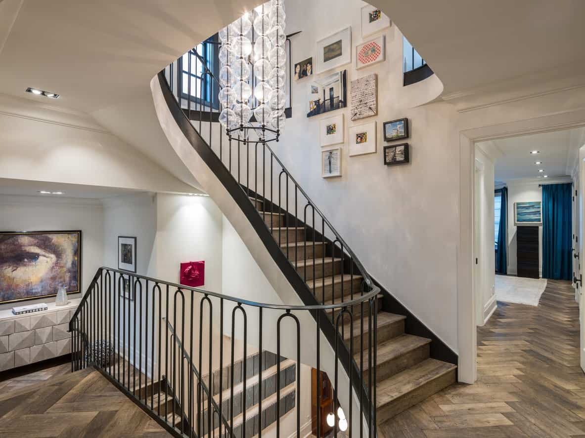 Iron and wood staircase with various wall art.