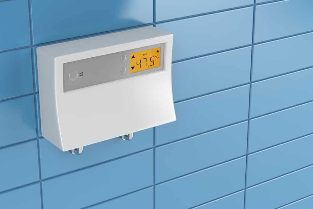 Tankless water heater mounted to a blue tile wall.