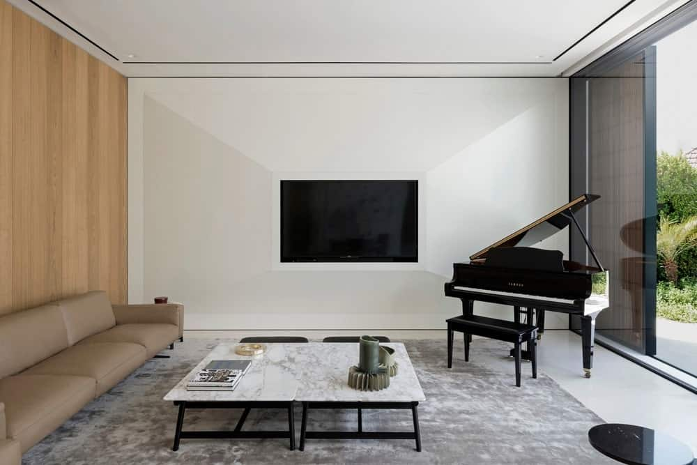 Modern living room furnished with a beige sectional sofa against the wood-paneled wall along with marble top coffee tables that sit on a gray area rug over white tiled flooring. It includes a wall-mount TV and a baby grand piano by the panoramic window bringing plenty of natural light in.