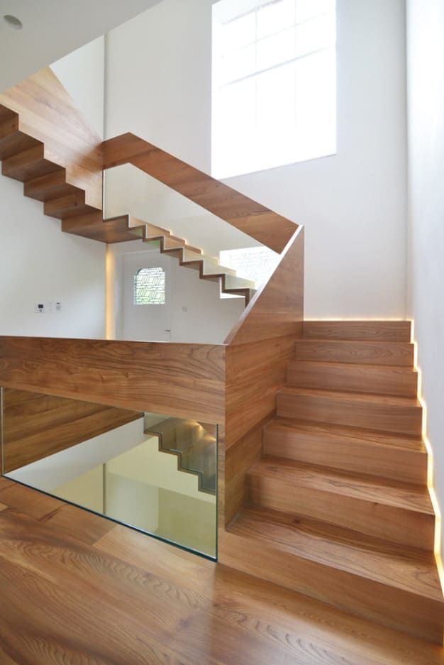 Charming wood staircase with glass balustrade framed with wood panel and fixed against white walls.