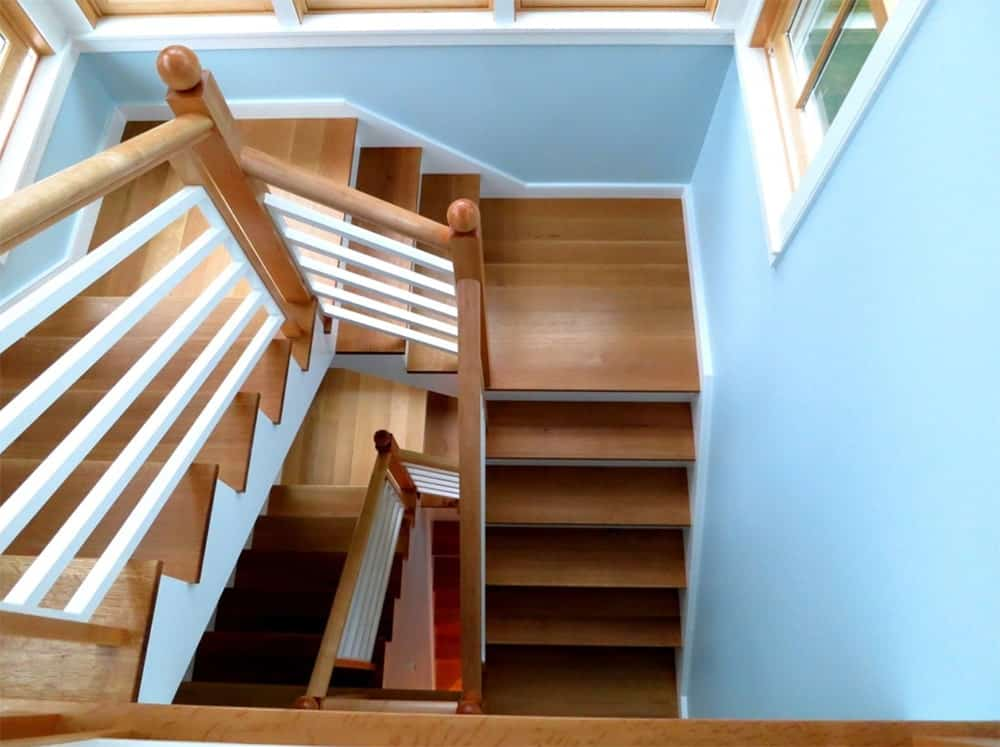 Wooden three-quarter turn staircase with white railings on blue walls accented with white crown moldings.