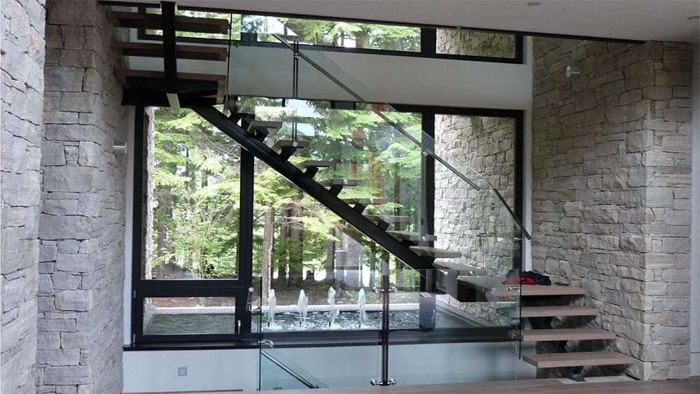 An open riser staircase with wooden treads and black mono stringer framed with glass railings. It is placed between stone brick walls with gorgeous water feature in the middle.