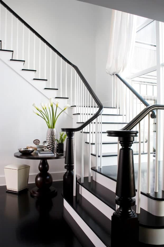 White staircase beautifully contrasted with black treads and handrails for a sophisticated look. There's a matching round table paired with a white stool on its front.