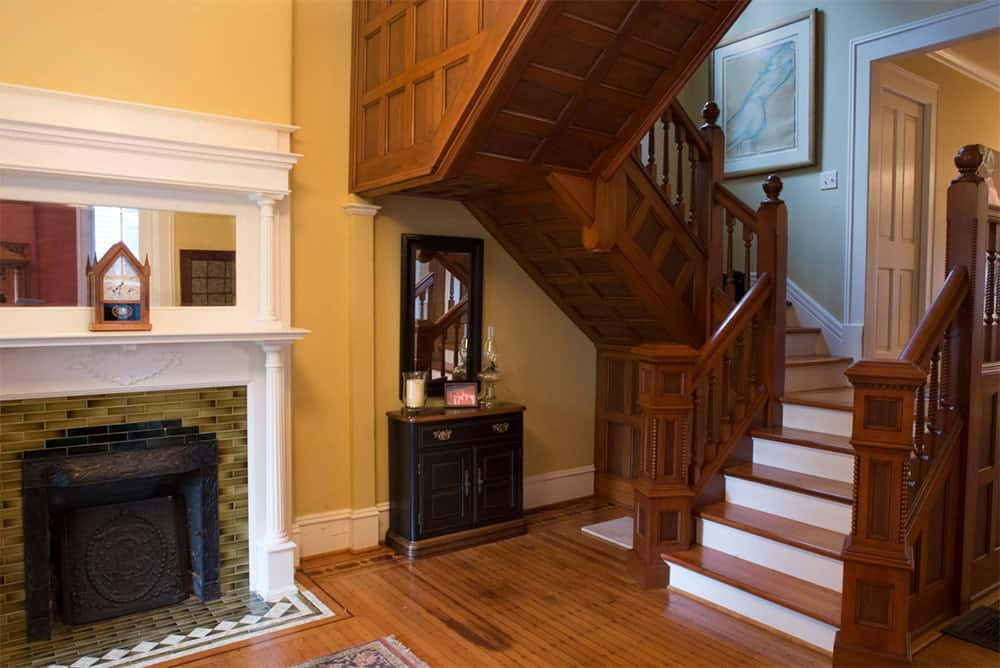 A rich wood staircase accented with white risers along the fireplace. There's a wooden framed mirror that hung over a cabinet underneath the stairs.