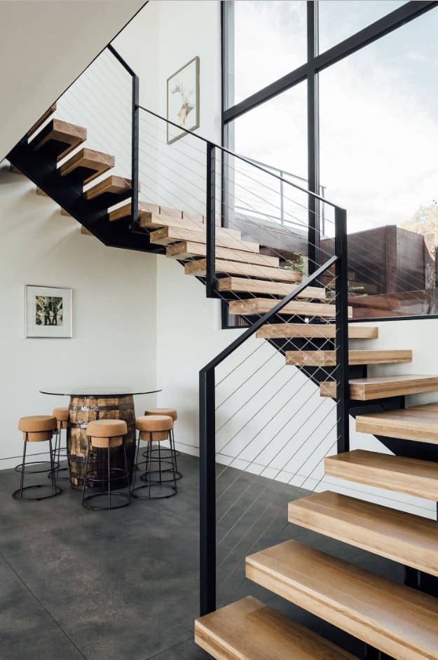 Floating wooden staircase with mono stringer and thin steel railings. It is accompanied with a round glass top table surrounded with cork stools in the corner.