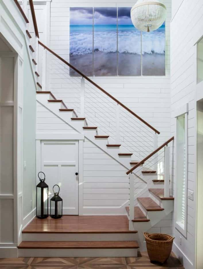 Beach style staircase fitted with wooden treads along the white shiplap walls It is designed with a lovely wall art and lanterns.