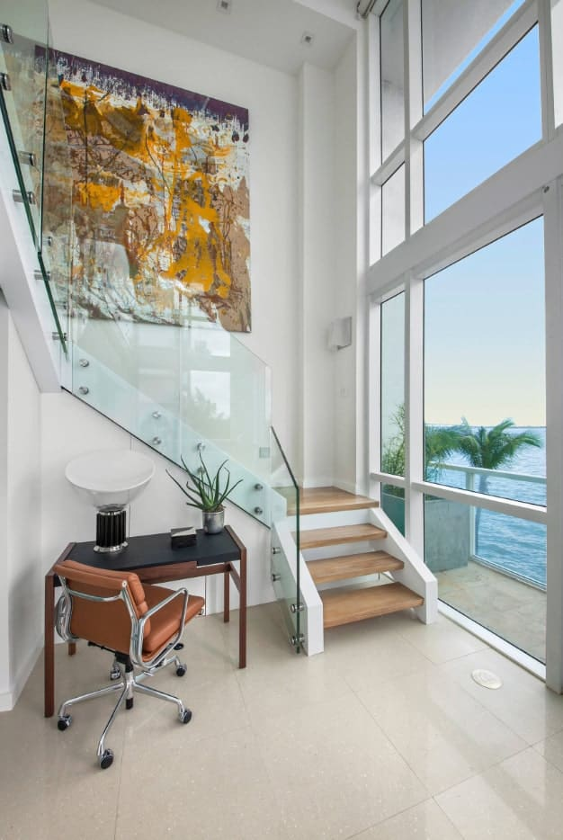 Contemporary staircase decorated with a huge abstract wall art. It has frameless glass railings and light wood treads with no risers.