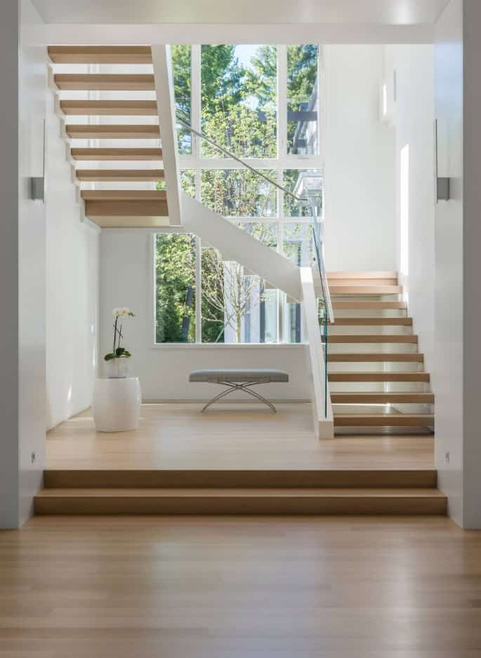 Wooden three-quarter turn staircase sits on the matching platform along with a cushioned bench and plant decor. They are illuminated with natural lights that stream through the white paneled windows.