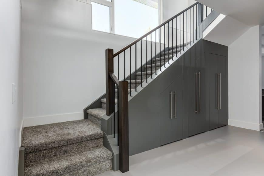 Sleek staircase covered with gray carpet features built-in gray storage underneath. It has wrought iron spindles and dark wood rail post.