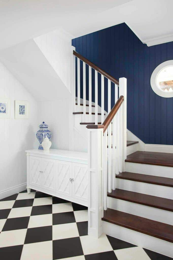 White staircase with wooden treads and handrails accented with deep blue shiplap walls and striking black and white diamond patterned floor.