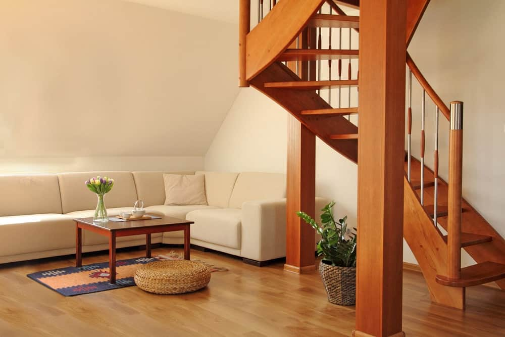 An open riser wooden staircase situated in the corner of the white living room. It complements the coffee table and hardwood flooring.