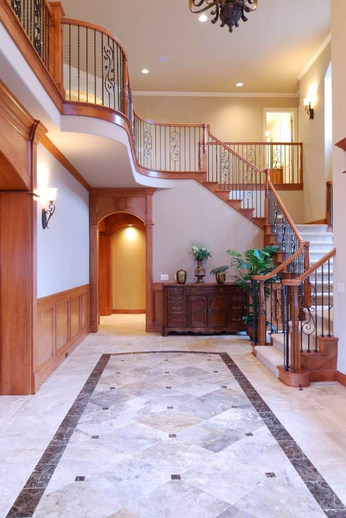 Elegant staircase boasts ornate iron balustrade along with wooden handrail and post. It has marble treads that match the flooring.
