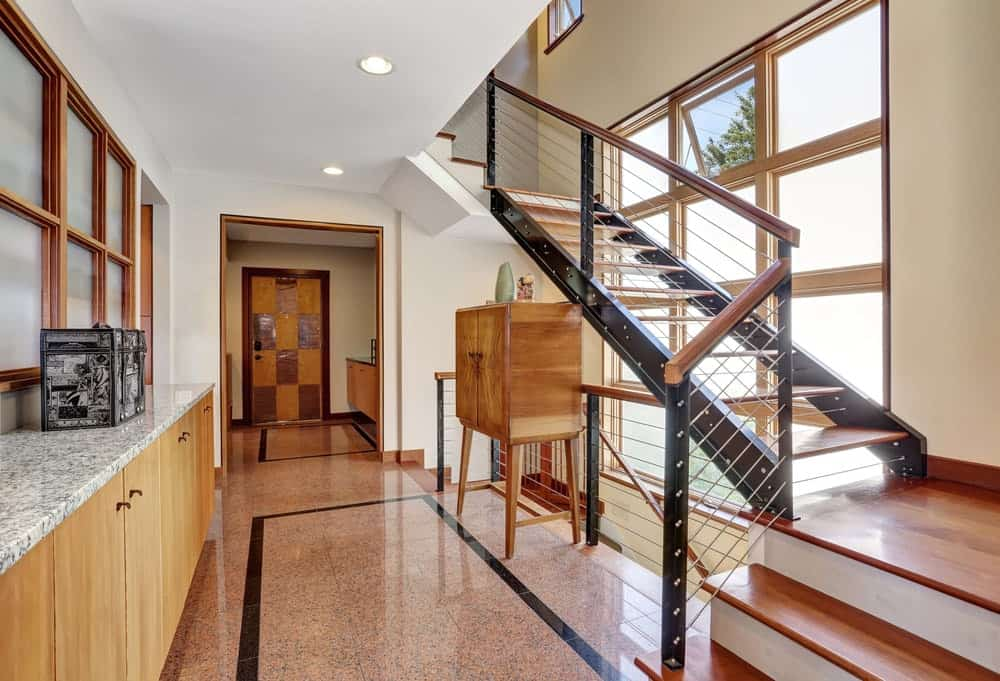 A three-quarter turn staircase lined with black stringers. It has wooden treads and thin steel railings. There's a tall wooden console table beneath it facing a matching cabinetry topped with granite counter.