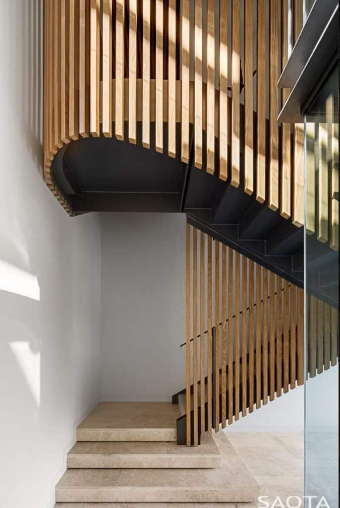 A spectacular marble staircase covered with wooden balustrade that beautifully flows along the second level.