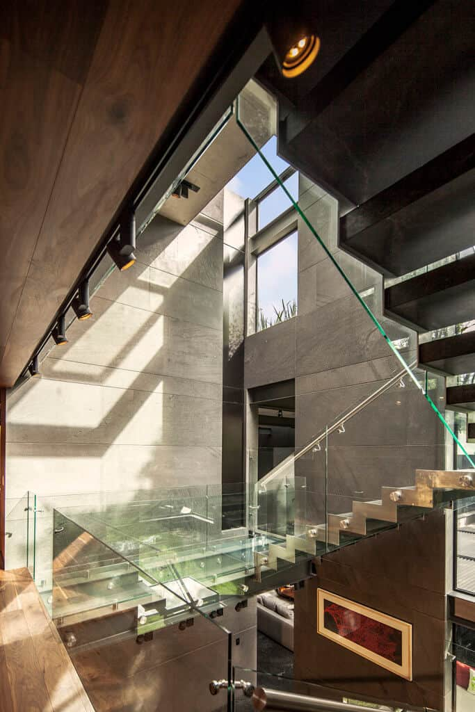 Modern design staircase showcases a steel zig-zag stringer framed with glass railings along the hardwood flooring and concrete paneled walls.