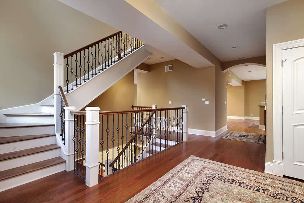 A two-toned staircase accented with ornate spindles against the taupe walls. It has wooden treads that match the hardwood flooring.