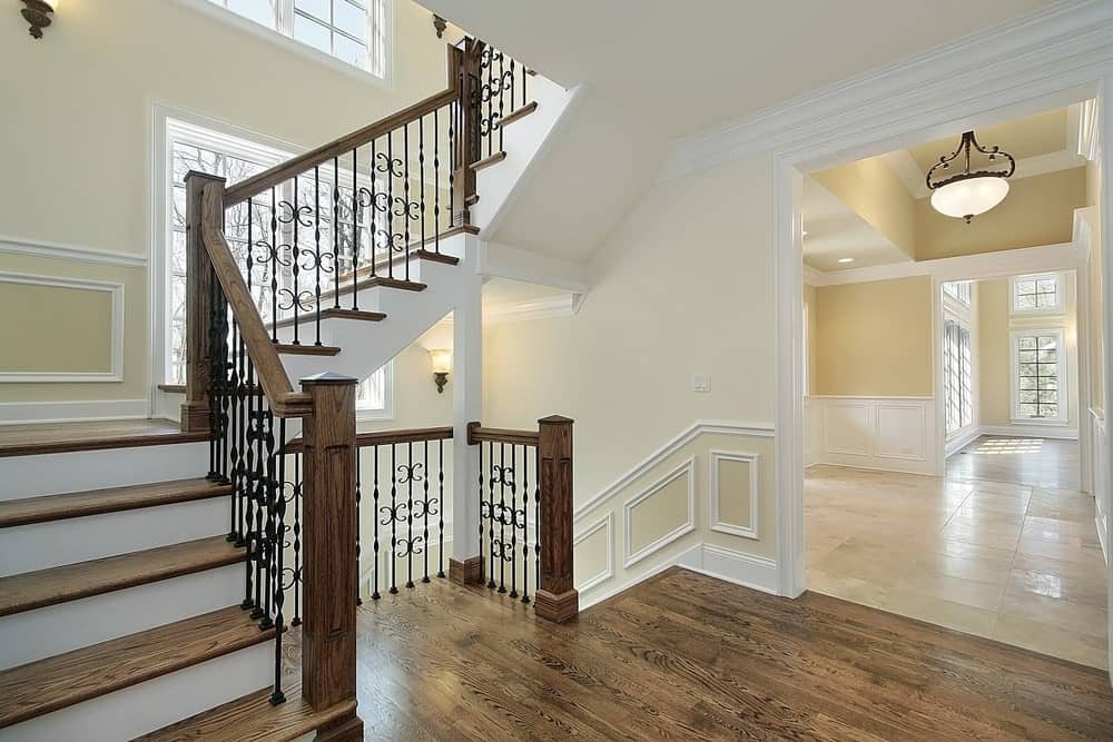 Three-quarter turn staircase boasts decorative railings lined with wooden handrails along the cream walls with wainscoting.