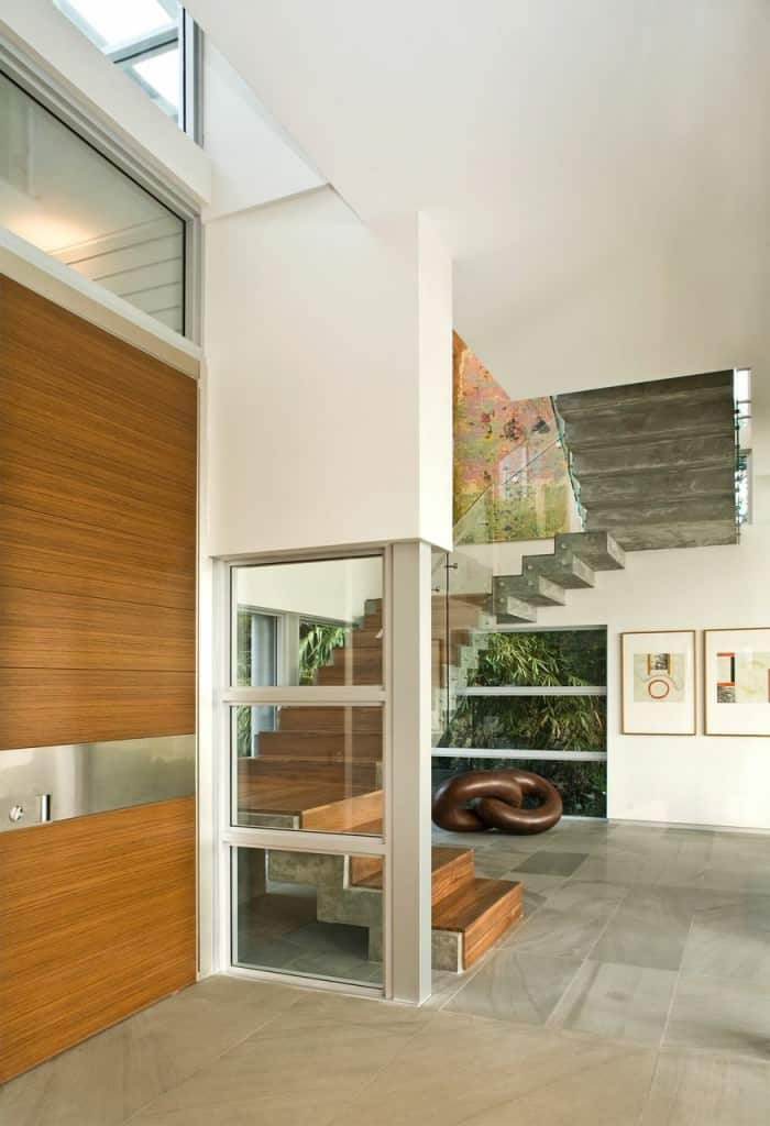 A contemporary staircase with concrete stringer contrasted with wooden treads and risers. It includes glass balustrade with mounted steel handrails.