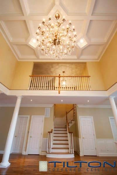 High narrow staircase with wood treads and white risers. The area is lighted by a grand luxurious chandelier that hung from a coffered ceiling.
