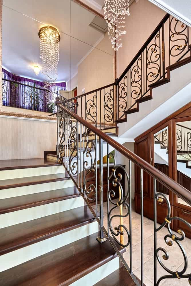 A closeup look of the elegant staircase with ornate railings lighted by fancy crystal chandeliers.