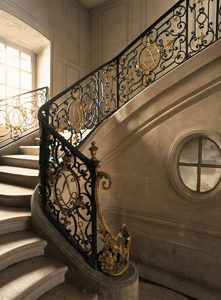 Closer look at the concrete grand staircase fixed with elegant balustrade that adds a timeless look.