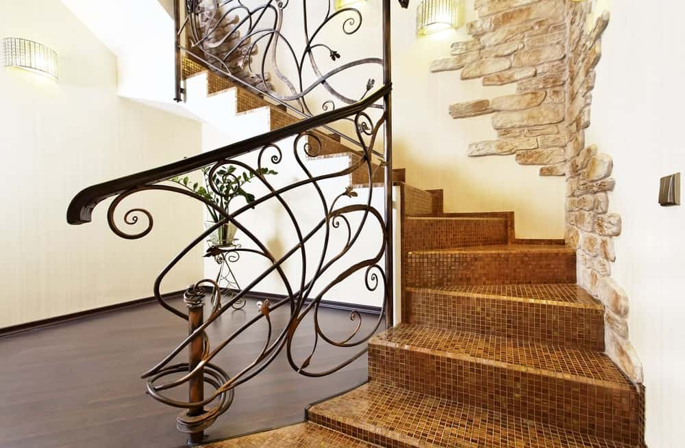 Glamorous staircase with decorative balustrade and mosaic tiles steps fixed against white walls accented with beautiful stone bricks.
