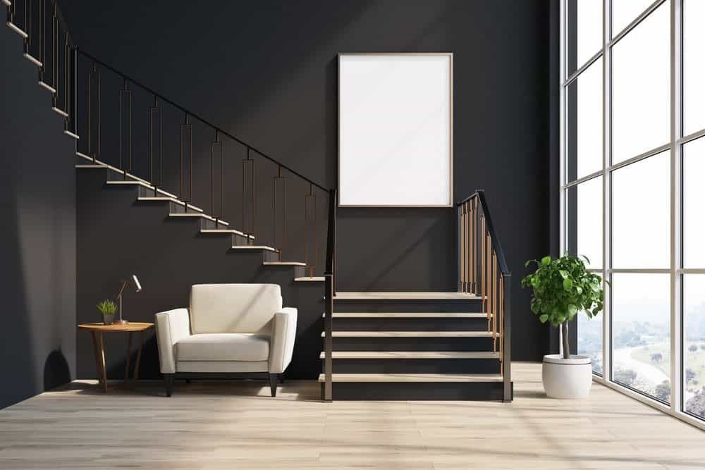 Black staircase with light wood treads and ornate spindles camouflaged on the black wall. A white upholstered chair paired with a wooden side table sits in the corner.