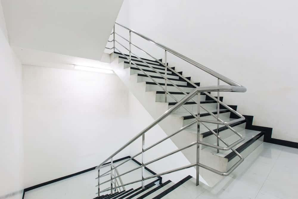 A sleek white tiled staircase with black lining framed with stainless steel railings.
