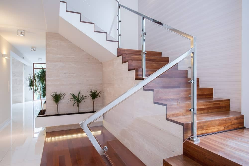 Rich hardwood staircase with glass balustrade framed with steel handrail and post. There's a built-in indoor planter beneath it.