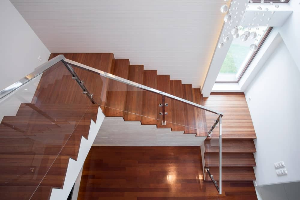 Sophisticated redwood staircase features glass railings lined with stainless steel handrails against the white walls.