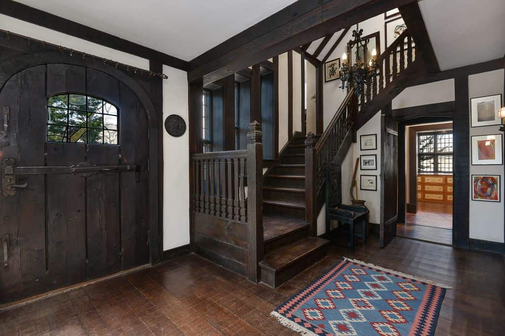 Vintage dark wood staircase complements the arched entry door with glass panels. It is designed with a black chandelier and multi-colored rug.