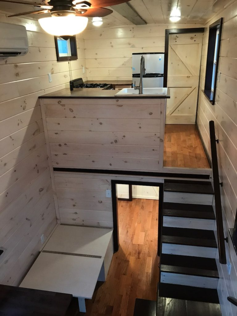 Another wooden staircase with wooden handrails from Incredible Tiny Homes. This one is unique as the staircase leads us to the kitchen instead of the usual loft area