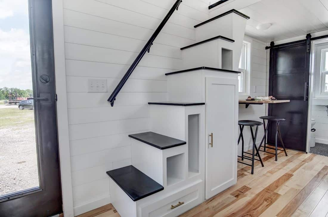 A modern staircase design that's light and bright. It might seem small but it has actually enough shelves and cabinets. It has also a handrail attached to the wall for support.